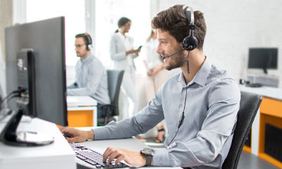 Our service process teaser image shows a man wearing a headset talking on the phone while looking at a computer