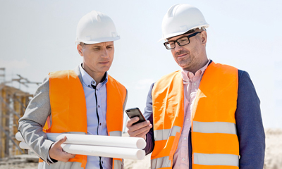 Two men on construction site in hi vis vests looking at a mobile phone, using Connect Fleet's Mobile device management solution